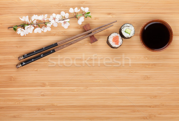 Sushi maki with fresh sakura branch over bamboo table Stock photo © karandaev