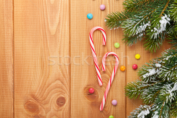 Christmas wooden background with snow fir tree and candies Stock photo © karandaev