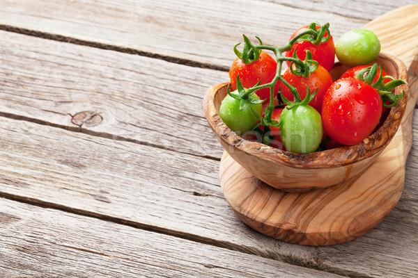 Pomodorini ciotola tavolo in legno view copia spazio alimentare Foto d'archivio © karandaev