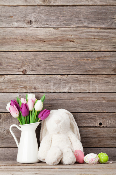 Rabbit toy, easter eggs and colorful tulips Stock photo © karandaev