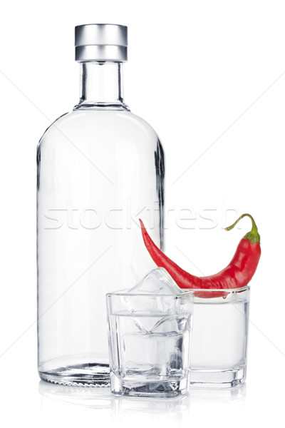Bottle of vodka and shot glass with ice and red chili pepper Stock photo © karandaev
