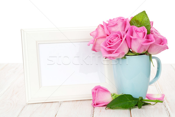 Blank photo frame and pink roses bouquet in tea cup Stock photo © karandaev
