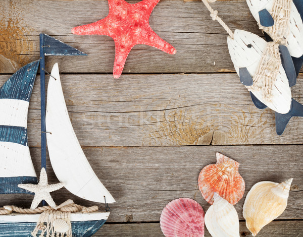Toy sailboat and fish with seashells and starfish on a wooden ba Stock photo © karandaev