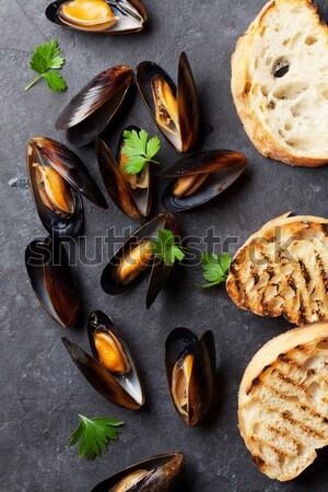 Fresh seafood on stone table. Scallops and shrimps Stock photo © karandaev