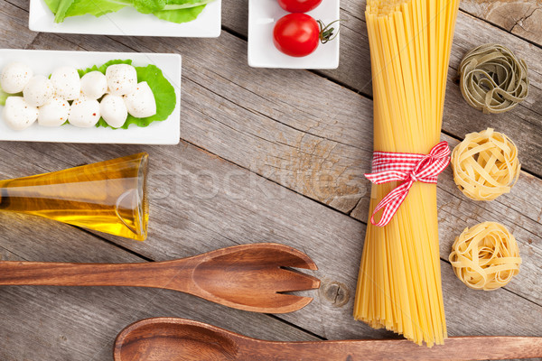 Tomatoes, mozzarella, pasta and green salad leaves Stock photo © karandaev