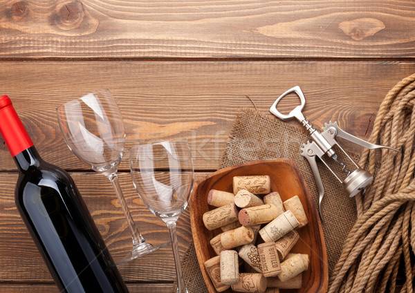 Red wine bottle, glasses, bowl with corks and corkscrew Stock photo © karandaev
