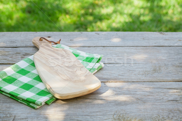 Empty garden table with cutting board over tablecloth Stock photo © karandaev