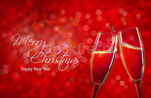 Two champagne glasses over red christmas background Stock photo © karandaev