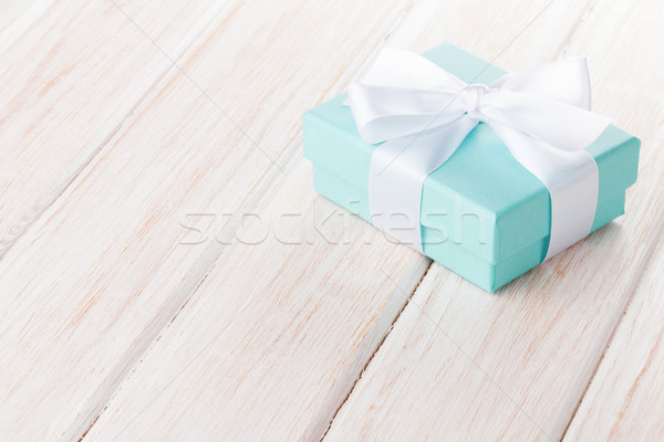 Gift box with bow over white wooden table Stock photo © karandaev