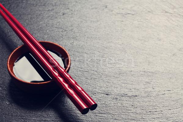 Japanese sushi chopsticks over soy sauce bowl Stock photo © karandaev