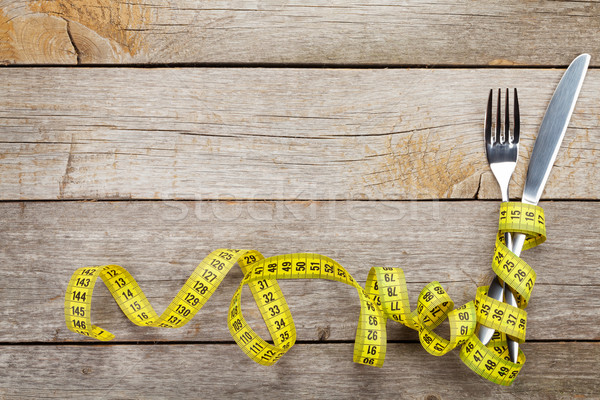 Measure tape with knife and fork. Diet food Stock photo © karandaev