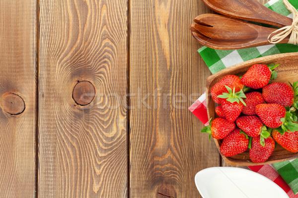 Fresco maduro morango tigela leite mesa de madeira Foto stock © karandaev