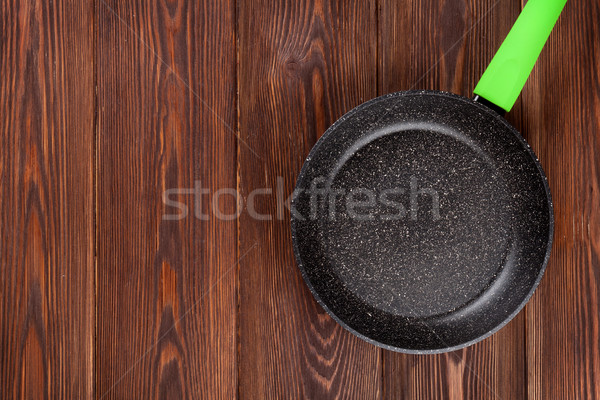 Frying pan on wooden table Stock photo © karandaev