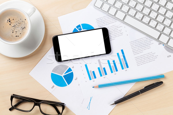 Office desk workplace with phone, charts and coffee Stock photo © karandaev