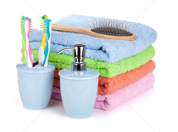 Four toothbrushes, liquid soap, hairbrush and colorful towels Stock photo © karandaev
