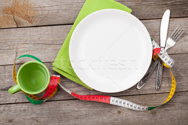Plate with measure tape, cup, knife and fork. Diet food on woode Stock photo © karandaev