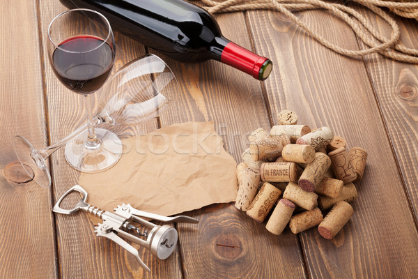 Glass of red wine, bottle and corkscrew on rustic wooden table Stock photo © karandaev