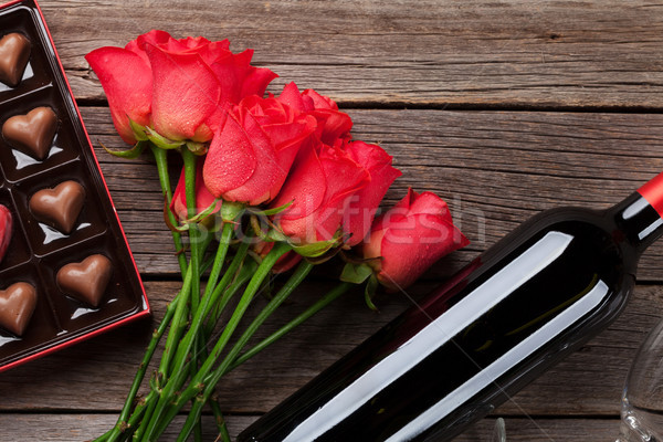 Red roses, wine bottle and chocolate box Stock photo © karandaev