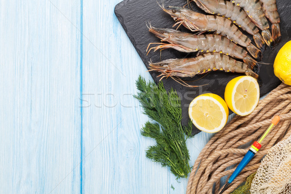 Fresh raw tiger prawns and fishing equipment Stock photo © karandaev