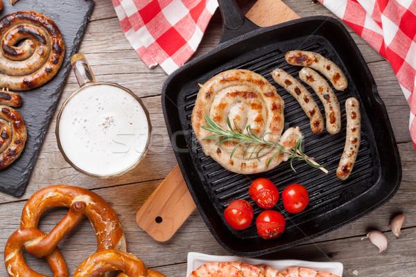 Cerveja caneca grelhado salsichas pretzel mesa de madeira Foto stock © karandaev