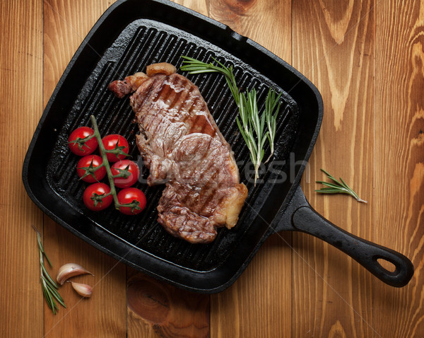Sirloin steak with rosemary and cherry tomatoes on frying pan Stock photo © karandaev