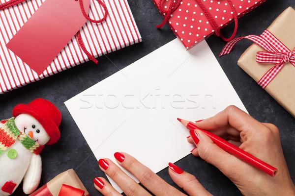 Female writing christmas greeting card and gift wrapping Stock photo © karandaev
