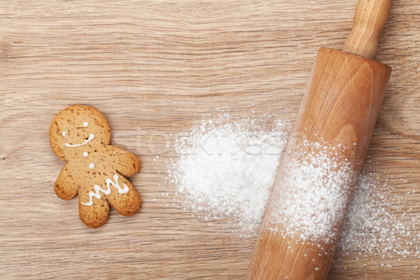 Rolling pin with flour and gingerbread cookie on wooden table Stock photo © karandaev