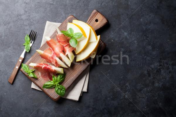 Melon with prosciutto and basil Stock photo © karandaev
