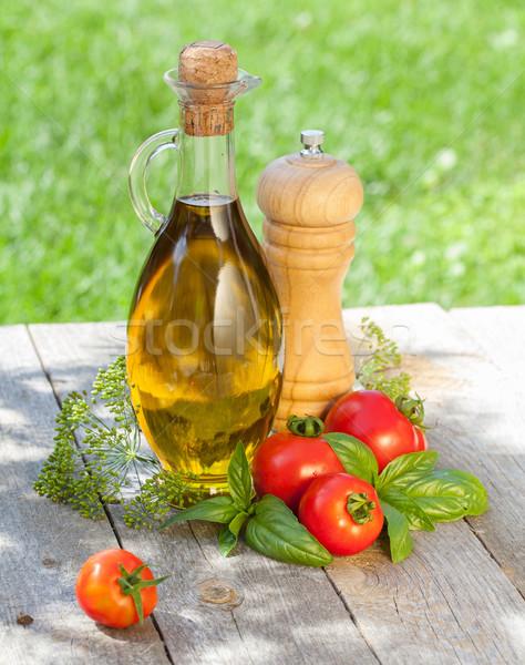 Olive oil bottle, pepper shaker, tomatoes and herbs Stock photo © karandaev