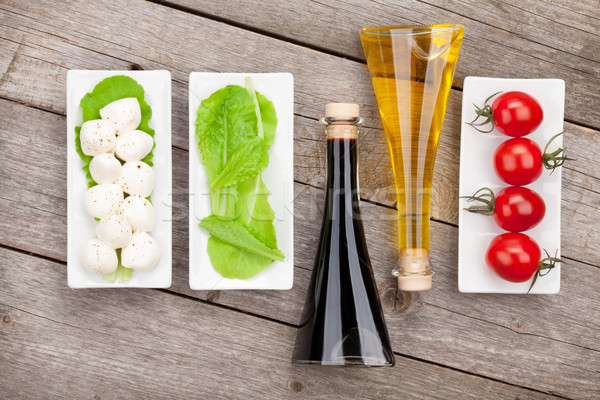 Tomatoes, mozzarella and green salad leaves with condiments Stock photo © karandaev