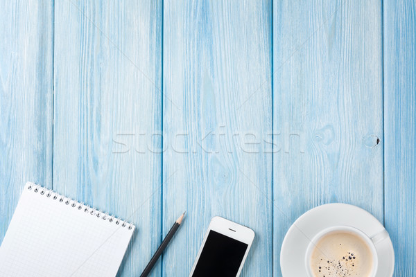Coffee cup, smartphone and blank notepad on wooden table backgro Stock photo © karandaev