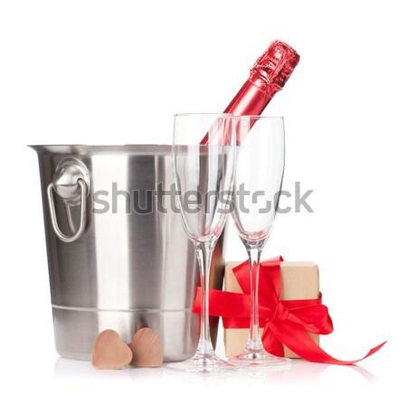 Champagne bottle, two glasses, gift box and red rose flowers Stock photo © karandaev