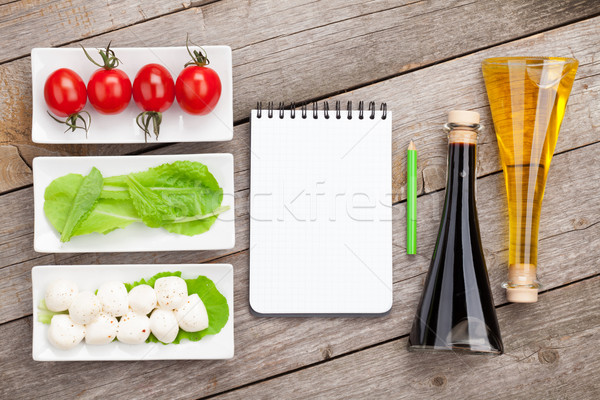 Tomatoes, mozzarella and green salad leaves with notepad for cop Stock photo © karandaev
