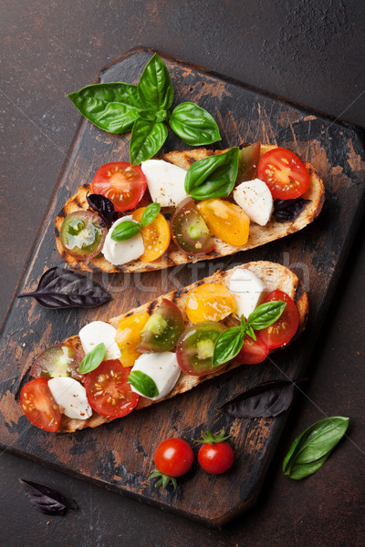 Bruschetta with tomatoes, mozzarella and basil Stock photo © karandaev