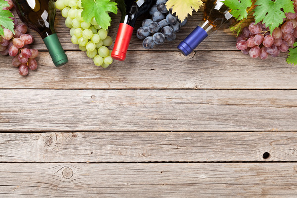 Foto d'archivio: Vino · bottiglie · uve · tavolo · in · legno · top · view