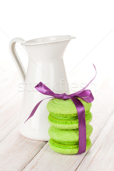 Green macarons with purple ribbon and milk jug Stock photo © karandaev