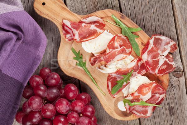 Prosciutto mozzarella tábla szőlő vágódeszka fa asztal Stock fotó © karandaev