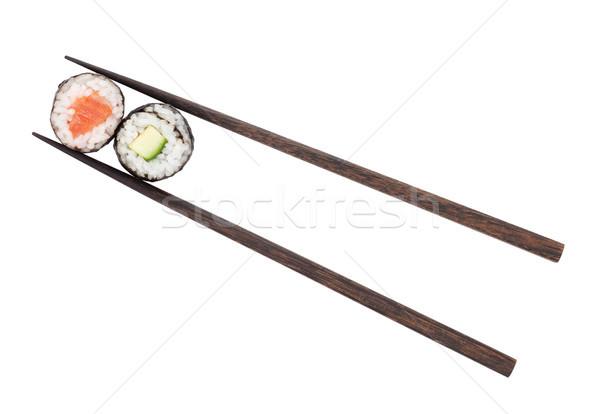 Sushi maki with salmon and cucumber in chopsticks Stock photo © karandaev