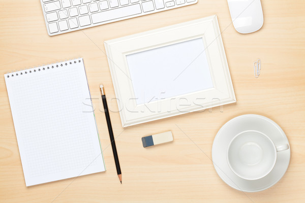 Stock photo: Photo frame on office table with notepad, computer and coffee cu