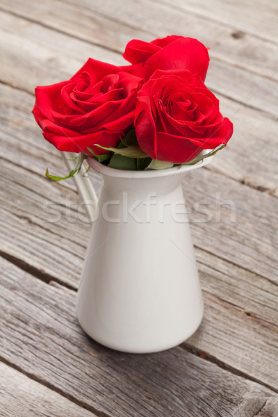 Red rose flowers in pitcher Stock photo © karandaev