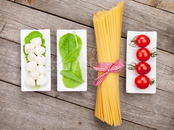 Tomatoes, mozzarella, pasta and green salad leaves Stock photo © karandaev