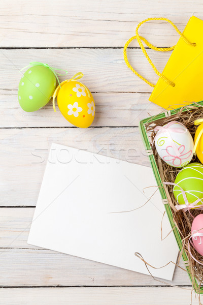 Easter background with colorful eggs, yellow tulips and greeting Stock photo © karandaev