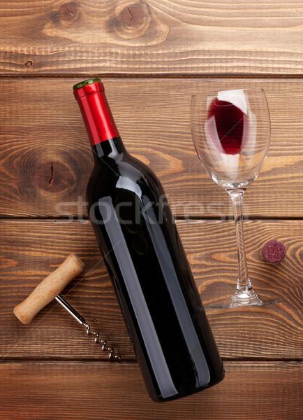 Red wine bottle, glass and corkscrew on wooden table Stock photo © karandaev