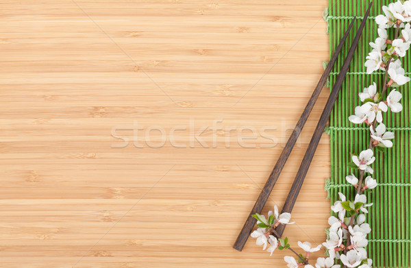 Chopsticks and sakura branch over bamboo mat Stock photo © karandaev