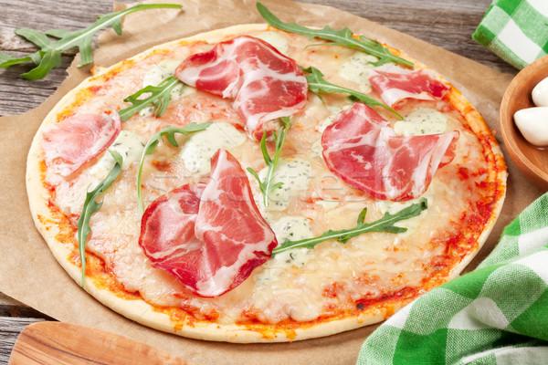 Pizza prosciutto mozzarella fa asztal közelkép papír Stock fotó © karandaev
