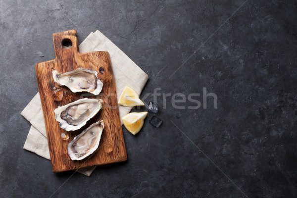 Oysters and lemon over ice Stock photo © karandaev