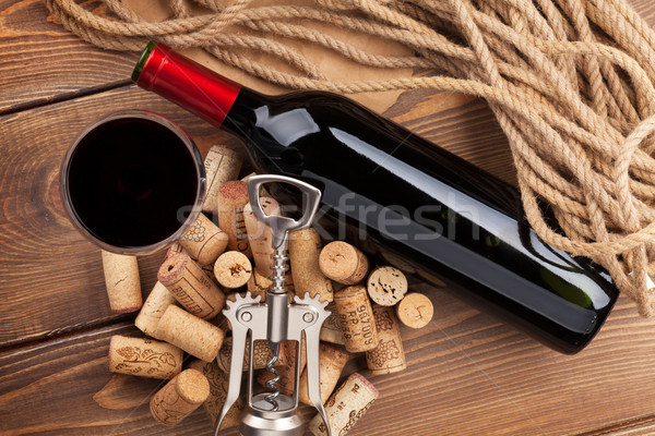 Red wine bottle, glass, corks and corkscrew. View from above Stock photo © karandaev