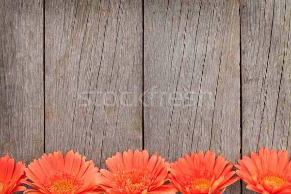 Wooden background with orange gerbera flowers Stock photo © karandaev