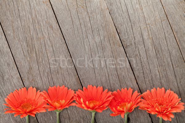 Wooden background with orange gerbera flowers Stock photo © karandaev