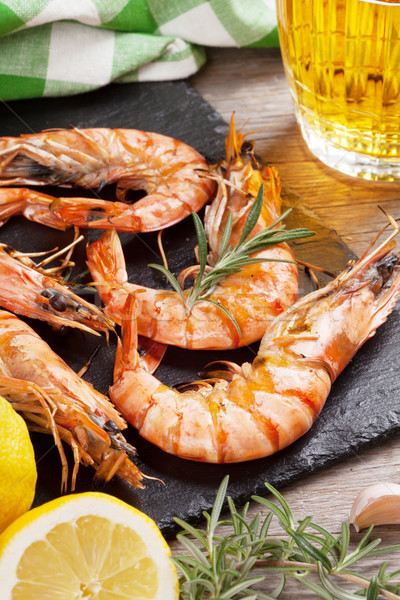 Grilled shrimps on stone plate and beer mug Stock photo © karandaev